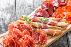 开胃小菜盛肉盘冷盘板材用grissini面包条、熏火腿,切片火腿,牛肉干,蒜味咸腊肠和芝麻菜在船上 库存照片