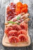 开胃小菜盛肉盘冷盘板材用grissini面包条、熏火腿,切片火腿,牛肉干,蒜味咸腊肠和芝麻菜在船上 免版税库存照片