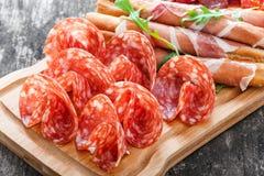 开胃小菜盛肉盘冷盘板材用grissini面包条、熏火腿,切片火腿,牛肉干,蒜味咸腊肠和芝麻菜 图库摄影