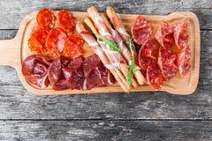 开胃小菜盛肉盘冷盘板材用grissini面包条、熏火腿,切片火腿,牛肉干,蒜味咸腊肠和芝麻菜 免版税库存图片