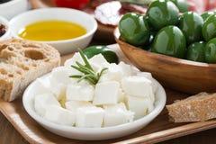 开胃小菜盛肉盘-新鲜的希腊白软干酪、橄榄和ciabatta 库存照片