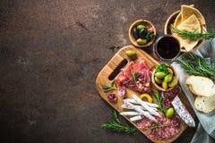 开胃小菜-切的肉、火腿、蒜味咸腊肠、橄榄和玻璃酒 免版税库存照片