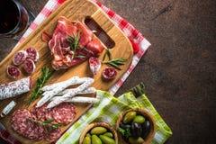 开胃小菜-切的肉、火腿、蒜味咸腊肠、橄榄和酒顶视图 免版税库存图片