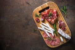 开胃小菜-切的肉、火腿、蒜味咸腊肠、橄榄和酒顶视图 图库摄影