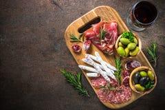 开胃小菜-切的肉、火腿、蒜味咸腊肠、橄榄和酒顶视图 免版税库存照片