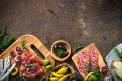 开胃小菜-切的肉,火腿,蒜味咸腊肠,在黑暗的石桌上的橄榄 库存图片