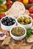 开胃小菜-橄榄, pesto和面包的分类,垂直 图库摄影