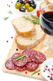 开胃小菜-蒜味咸腊肠、红葡萄酒被隔绝的面包、橄榄和杯 免版税库存照片