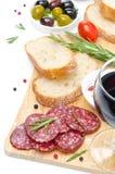 开胃小菜-蒜味咸腊肠、面包、橄榄和杯酒  免版税图库摄影