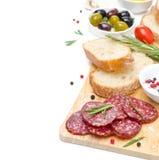 开胃小菜-蒜味咸腊肠,面包,橄榄,在白色隔绝的蕃茄 免版税图库摄影