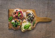 开胃小菜brusquetta在麻袋布的一个土气木板设置了 库存图片