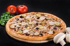 开胃新鲜的薄饼用蘑菇、烟肉、橄榄、葱和p 免版税库存照片