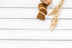 开胃新鲜面包概念 在麦子的耳朵的附近切的大面包在白色木背景顶视图拷贝空间的 免版税库存照片