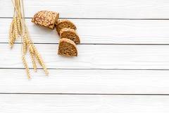 开胃新鲜面包概念 在麦子的耳朵的附近切的大面包在白色木背景顶视图拷贝空间的 库存照片