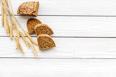 开胃新鲜面包概念 在麦子的耳朵的附近切的大面包在白色木背景顶视图拷贝空间的 免版税库存图片