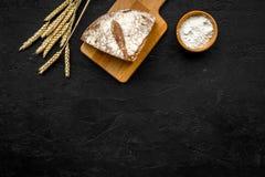 开胃新鲜面包概念 在麦子的耳朵的附近切的大面包在黑背景顶视图拷贝空间的 图库摄影