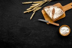 开胃新鲜面包概念 在麦子的耳朵的附近切的大面包在黑背景顶视图拷贝空间的 库存照片