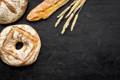 开胃新鲜面包概念 长方形宝石和圆的大面包在麦子的耳朵附近在黑背景顶视图复制空间 免版税库存图片