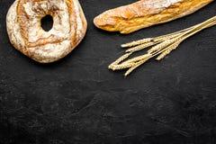 开胃新鲜面包概念 长方形宝石和圆的大面包在麦子的耳朵附近在黑背景顶视图复制空间 库存照片