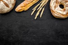 开胃新鲜面包概念 长方形宝石和圆的大面包在麦子的耳朵附近在黑背景顶视图复制空间 免版税库存照片