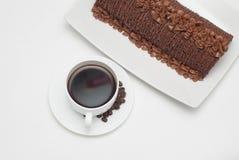 开胃杯热的咖啡在背景中服务与巧克力蛋糕 查出 顶视图 免版税图库摄影