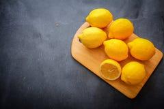 开胃柠檬,一在黑暗的背景的一个轻的木板切开了 免版税图库摄影