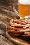 开胃格栅香肠和低度黄啤酒,关闭 免版税库存照片
