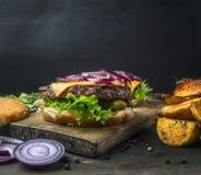 开胃水多的家庭汉堡用牛肉、沙拉、酱瓜、乳酪和葱,土豆,楔子,小圆面包用芝麻,在葡萄酒c 库存图片