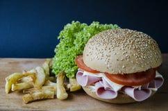 开胃汉堡三明治用乳酪香肠蕃茄和沙拉用一个土豆在木平台有一张蓝纸的 库存照片