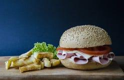 开胃汉堡三明治用乳酪香肠蕃茄和沙拉用一个土豆在木平台有一张蓝纸的 免版税库存图片