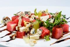 开胃沙拉用西瓜、乳酪和调味汁在白色pl 免版税库存图片