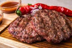 开胃油煎的牛肉炸肉排,装饰用草本,胡椒,用调味汁 水平的框架 免版税图库摄影