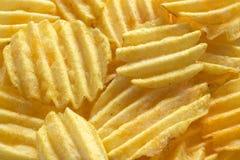 从开胃波纹状的土豆片的背景 免版税库存照片