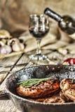 开胃烤牛排用迷迭香和酒在餐桌上 库存照片