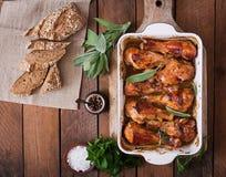 开胃烤箱烘烤了在烘烤盘的金黄小鸡腿在一张木桌上 库存照片