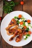 开胃烤箱烘烤了金黄小鸡腿和希腊沙拉 库存照片