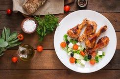 开胃烤箱烘烤了金黄小鸡腿和希腊沙拉 免版税图库摄影