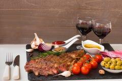开胃烤肉 在黑人石委员会、红葡萄酒和两个充分的酒杯的烤牛肉entrecote中等烘烤 最佳的晚餐 免版税库存照片