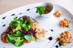 开胃烤鱼用蕃茄和莴苣 免版税库存照片