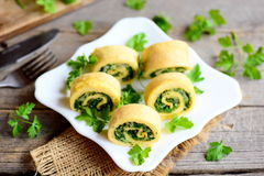 开胃煎蛋卷滚动用乳酪和绿色在一块白色板材和葡萄酒木桌 被充塞的被切的煎蛋卷食谱想法 库存图片