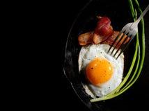 开胃煎蛋用烟肉和葱在黑背景 库存照片