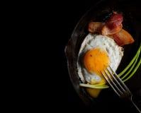 开胃煎蛋用烟肉和葱在黑背景 库存图片