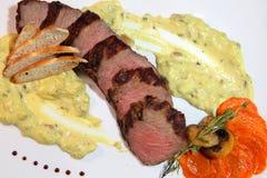 开胃牛排中等烘烤,裁减成在乳脂状的蘑菇酱油的片断 牛排在一张木桌上的白色板材服务 库存图片