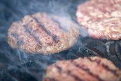 开胃牛肉汉堡包在与烟的BBQ格栅烤 免版税图库摄影