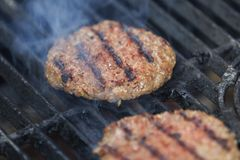 开胃牛肉汉堡包在与烟的BBQ格栅烤 库存照片