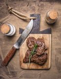 开胃牛肉,烤,在一个切板用迷迭香,香料和刀子肉木土气背景顶视图的结束u 免版税图库摄影