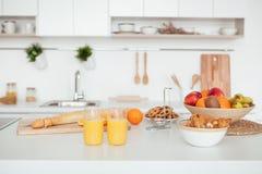 开胃甜橙站立在一张白色桌上的汁液和两水杯在breackfest的厨房里 库存照片