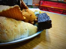 开胃甜点曲奇饼,新月形面包,在巧克力的薄酥饼在一张木桌上的一块板材说谎 免版税库存图片