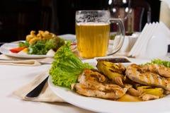 开胃盘和啤酒杯在表上 免版税图库摄影
