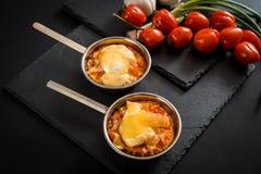 开胃肉用蘑菇,烘烤用在椰子的乳酪,在铁的两个小部分在西红柿附近作为b的一装饰 库存照片